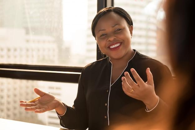 Freundlicher schwarzer geschäftsfrauführer, der arbeit bei der sitzung bespricht