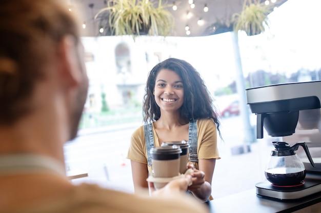 Freundlicher service. glückliche hübsche junge frau, die bestellten kaffee zum mitnehmen nimmt, der vor barista im café steht