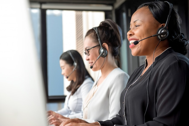 Freundlicher tragender mikrofonkopfhörer der schwarzen frau, der im kundenkontaktcenter arbeitet