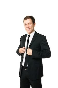 Freundlicher und lächelnder geschäftsmann, der die kamera mit zuverlässigkeit auf weißem hintergrund betrachtet
