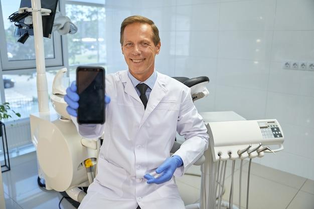 Freundlicher zahnarzt, der ein smartphone mit leerem bildschirm hält