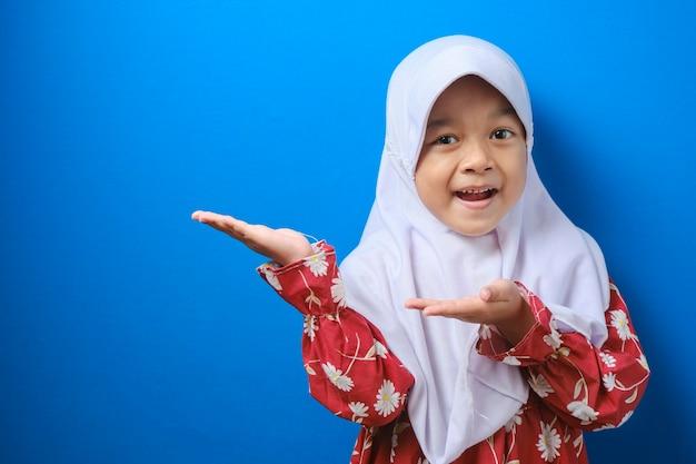 Freundliches asiatisches muslimisches mädchen, das mit beiden händen etwas an ihrer seite zeigt, isoliert auf blauem hintergrund