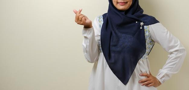Freundliches asiatisches muslimisches mädchen, das mit beiden händen etwas an ihrer seite zeigt, isoliert auf weißem hintergrund