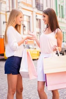 Freundliches gespräch. seitenansicht von zwei attraktiven jungen frauen, die sich unterhalten, während sie einkaufstaschen tragen und im freien stehen