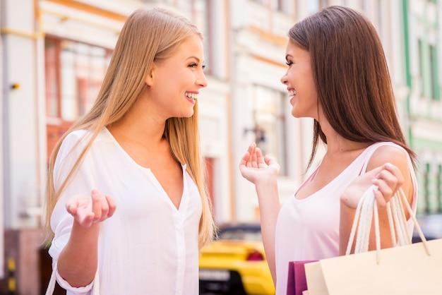 Freundliches gespräch. seitenansicht von zwei schönen jungen frauen, die sich unterhalten, während sie einkaufstaschen tragen und im freien stehen