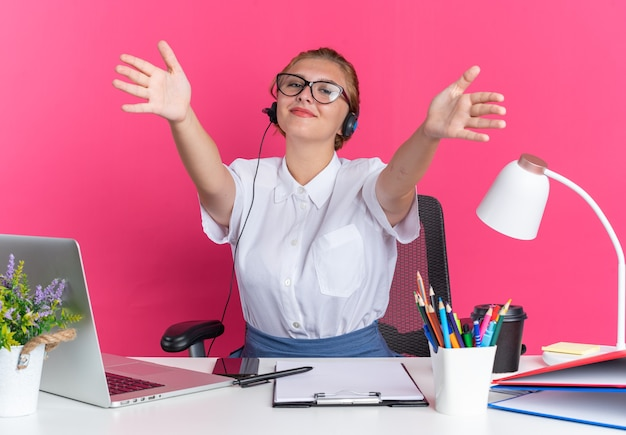 Freundliches junges blondes callcenter-mädchen mit headset und brille, das am schreibtisch mit arbeitswerkzeugen sitzt und eine willkommensgeste macht