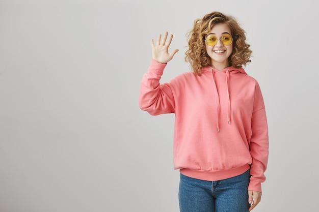 Freundliches junges mädchen in der sonnenbrille, die hallo sagt und handgruß winkt