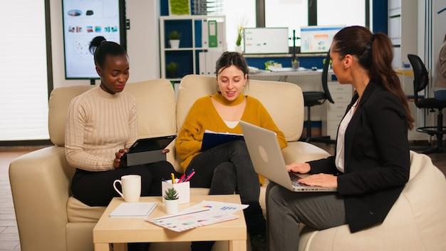 Freundliches, kreatives, vielfältiges kollegenteam, das über online-projekte mit laptop und tablet am arbeitsplatz diskutiert. gruppe von gemischtrassigen mitarbeitern, die zusammen arbeiten und marketingideen beim bürotreffen austauschen
