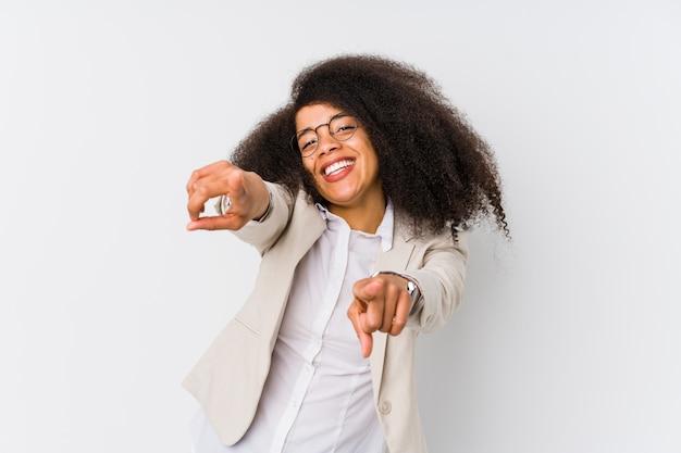 Freundliches lächeln der jungen afroamerikanergeschäftsfrau, das auf front zeigt.