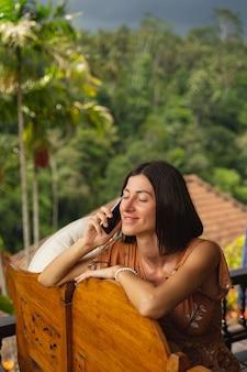 Freundliches lächeln. entspannte brünette weibliche person, die ihre augen geschlossen hält, während sie eine angenehme online-konversation genießt