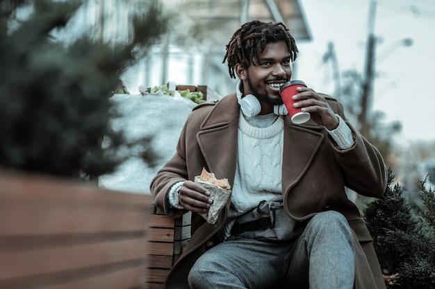 Freundliches lächeln. hübscher mann, der lächeln auf seinem gesicht hält, während er kaffeepause hat