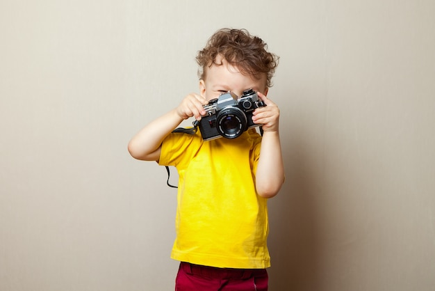 Freundliches lächelndes kind, das eine sofortige kamera anhält