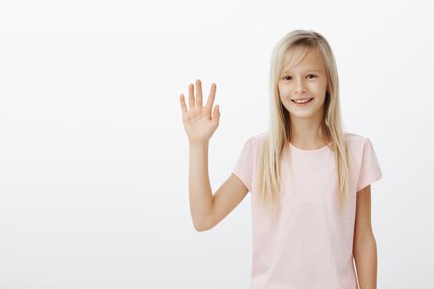 Freundliches lächelndes kind, das hallo sagt, kleine frau, die hand winkt, sagt hallo