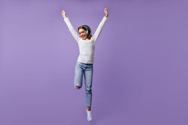 Freundliches mädchen in fröhlicher stimmung springt mit erhobenen armen. porträt des studenten in voller länge im weißen gespräch, das musik hört