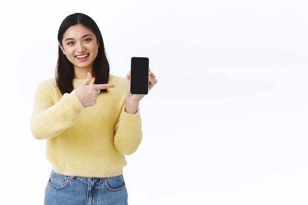 Freundliches süßes asiatisches mädchen, das ihnen bilder aus dem urlaub auf dem mobilen bildschirm zeigt, das smartphone hält und mit dem finger auf das display zeigt, amüsiert lächelt, ratschläge gibt, welchen link klickt, die unternehmenswebsite fördern