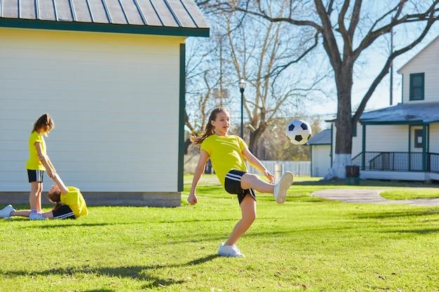 Freundmädchenjugendlich, der fußballfußball in einem park spielt