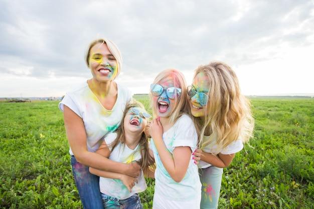 Freundschaft, feiertage, farbkonzept - porträt von schönen und glücklichen freunden, die mit farbe über naturoberfläche bedeckt sind