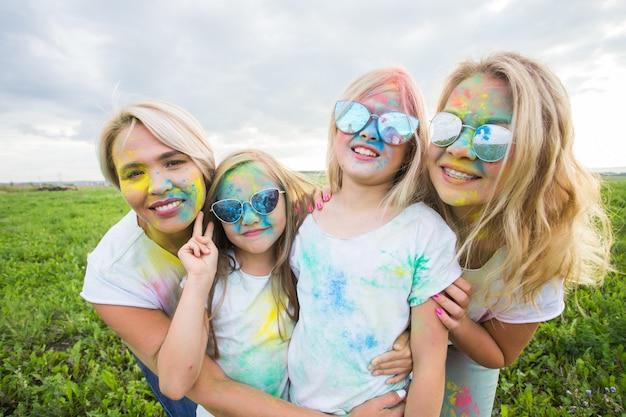 Freundschaft, feiertage, farbkonzept - porträt von schönen und glücklichen freunden, die mit farbe überzogen sind