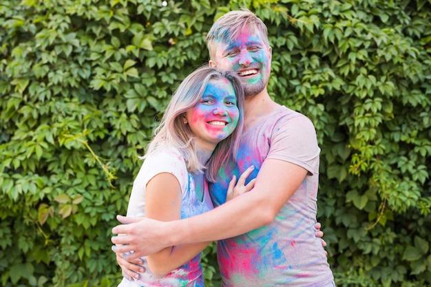 Freundschaft, festival of holi, people concept - junges paar, das beim festival von mit farben spielt