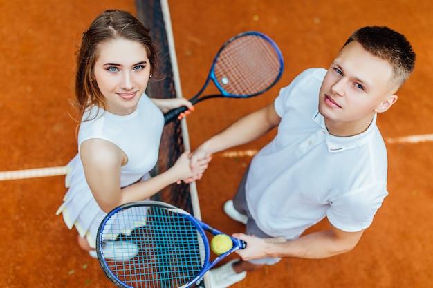 Freundschaft gewinnt. zwei überzeugte, hübsche hände rüttelnde und bei der stellung lächelnde tennisspieler nahe dem tennisnetz.