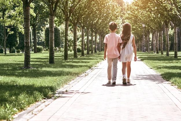 Freundschaft kleiner junge und mädchen, die auf der straße im park spazieren gehen