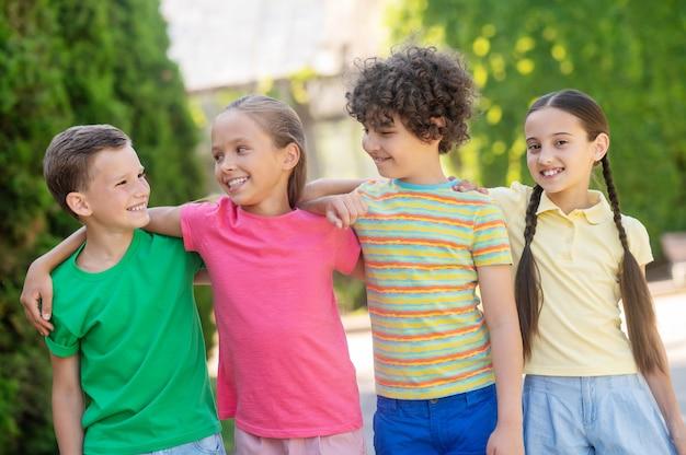 Freundschaft. lächelnde jungen und mädchen in heller freizeitkleidung, die am sommertag im grünen park umarmt stehen