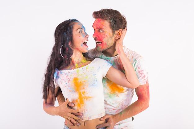 Freundschaft, liebe, fest des holi, menschenkonzept - junges paar spielt mit farben an der