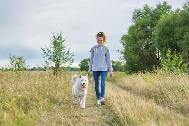 Freundschaft mädchen und hunde, teenager und haustier husky im freien gehen, schöne landschaft naturwiese bewölkten himmel