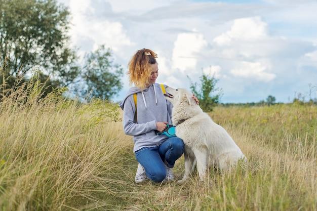 Freundschaft mädchen und hunde, teenager und haustier husky im freien gehen