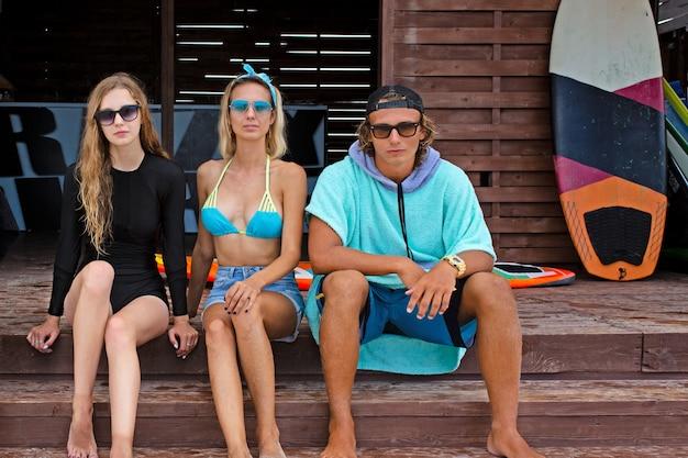 Freundschaft, meer, sommerferien, wassersport und personenkonzept - gruppe von freunden, die badebekleidung tragen, die mit surfbrettern am strand sitzt