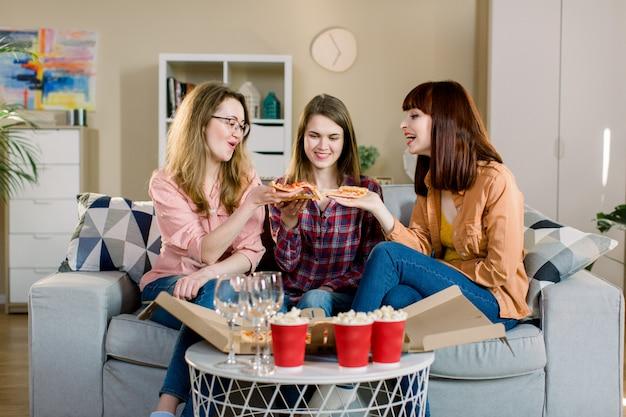 Freundschaft, menschen, pyjama-party und junk-food-konzept - glückliche junge drei frauen oder mädchen, die zu hause pizza, popcorn essen und wein trinken