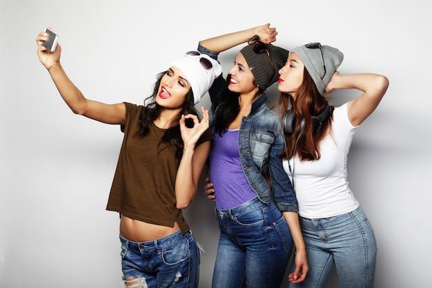Freundschaft, menschen und technologiekonzept - drei glückliche mädchen im teenageralter mit smartphone, die selfie machen