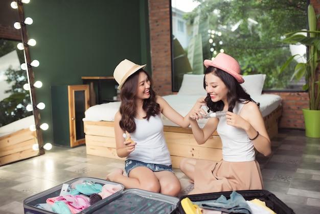 Freundschaft. reise. zwei asiatische junge freundinnen, die eine reisetasche packen, bevor sie in den urlaub fahren