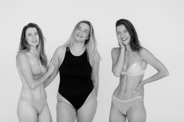Freundschaft schönheit körper positiv und menschen konzept gruppe von glücklichen frauen unterschiedlich in unterwäsche auf grauem hintergrund hochwertiges foto