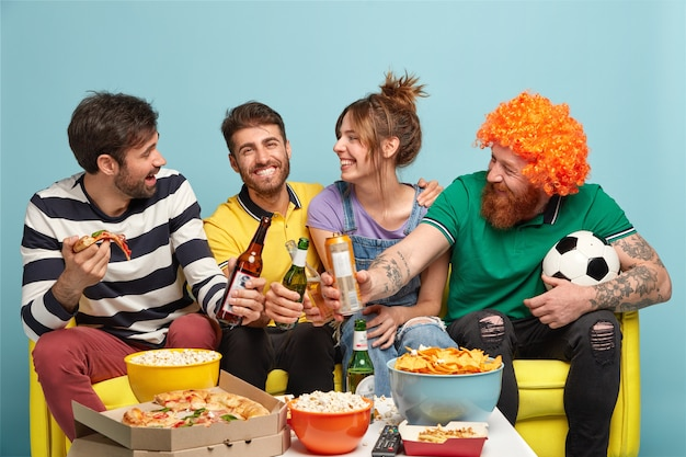 Freundschaft, sport, menschen, lifestyle-konzept. vier fröhliche freunde fußballfreunde schauen fußballspiel, feiern den sieg
