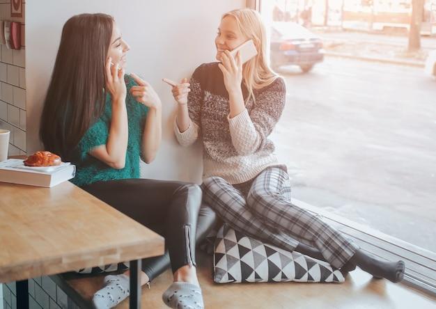 Freundschaft und technik. zwei hübsche mädchen, die smartphones benutzen, während sie im café tee oder kaffee trinken.
