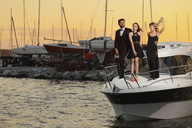 Freundschaft und urlaub. party auf der yacht. gruppe junger leute auf dem deck, das das meer segelt.