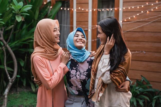 Freundschaft von drei frauen beim entspannen stehend auf dem haushof