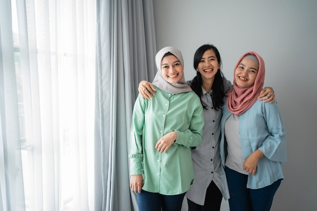 Freundschaft von drei lächelnden frauen, die neben einem fenster stehen