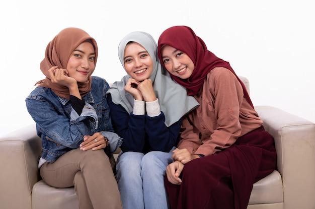Freundschaft von drei verschleierten frauen beim entspannen auf der couch sitzen