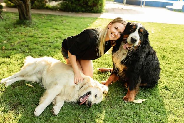 Freundschaft von menschen und tieren. frau, die mit hund labrador und sennenhund draußen im grünen park spielt.