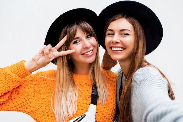 Freundschafts-, glücks- und menschenkonzept. zwei lächelnde mädchen flüstern klatsch auf weiß