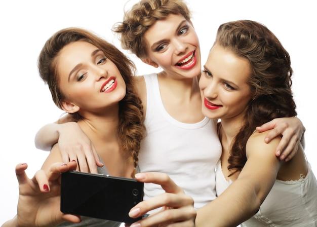 Freundschafts-, menschen- und technologiekonzept - drei glückliche teenager-mädchen mit smartphone, das selfie nimmt