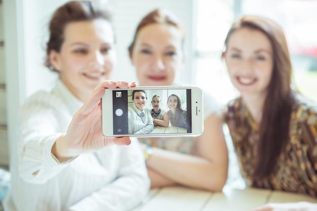 Freundschafts-, menschen- und technologiekonzept - glückliche freunde oder mädchen im teenageralter mit smartphone, das selfie nimmt
