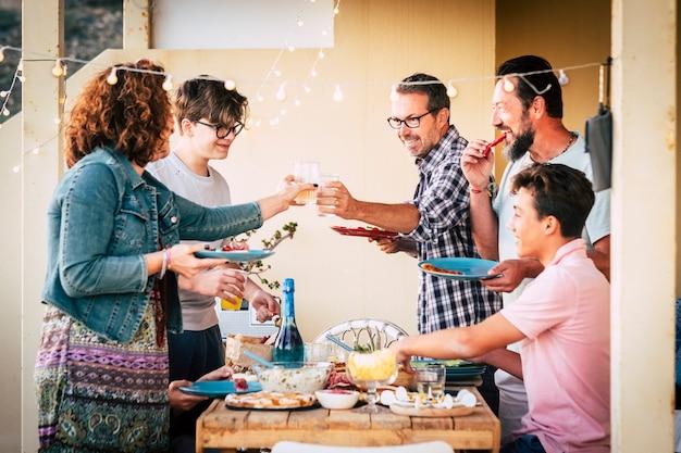 Freundschafts- und essenskonzept mit kaukasiern, die zu mittag oder zu abend essen, zusammen mit spaß und lachen - männer und frauen unterschiedlichen alters mit teenagern - holztisch und feierkonzept celebration