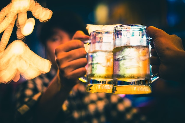 Freundschafts- und feierkonzept - glückliche männliche freunde, die klirrende gläser des bieres trinken