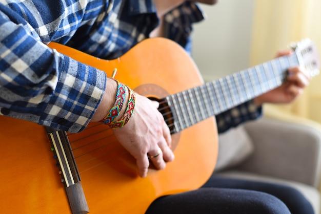 Freundschaftsbänder mit indischem muster am handgelenk des gitarristen