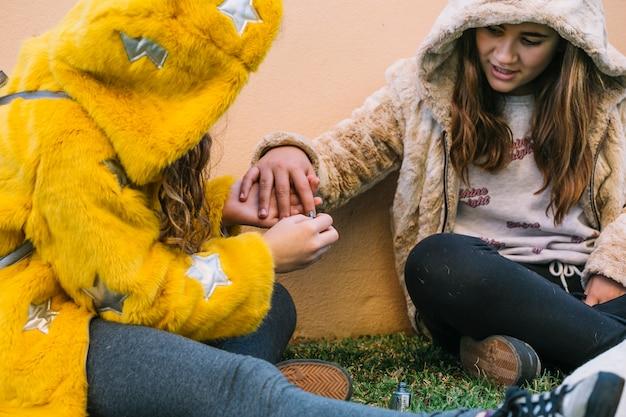 Freundschaftskonzept mit zwei mädchen, die nägel polieren