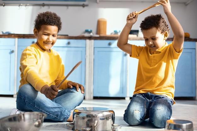 Freundschaftsziele. freudige kleine jungen sitzen mit gekreuzten beinen auf dem küchenboden und erzeugen geräusche, indem sie auf töpfen trommeln