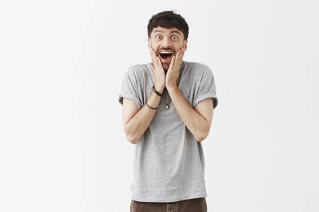 Freut sich über einen glücklichen, gutaussehenden mann, der gegen die weiße wand posiert